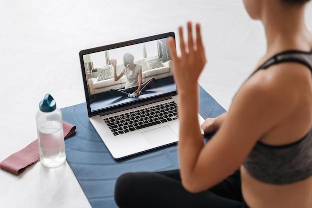Close up van jonge fit vrouw coach in sportkleding online fitnesstraining of virtuele yogales uitvoeren op een videoconferentie met laptop