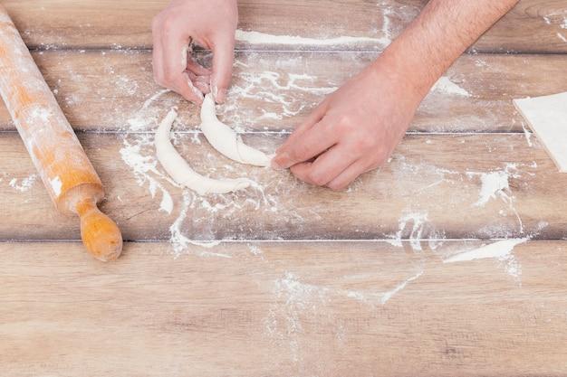 Close-up van jonge gebakjechef-kok die wat croissant op de lijst maken