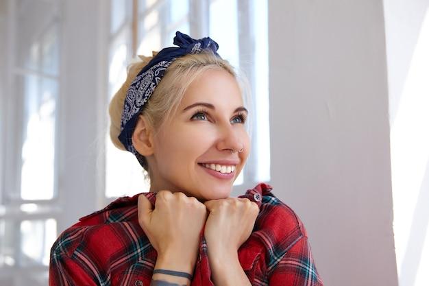 Close-up van jonge gelukkige blonde in hoofdband die haar gezicht op opgeheven handen leunt en vrolijk glimlacht, in goede bui is terwijl hij voor groot raam staat