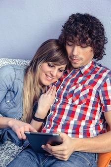 Close-up van jonge gelukkige paar verliefd omarmt op zoek naar elektronische tablet terwijl rusten over een bed. vrije tijd thuis concept.