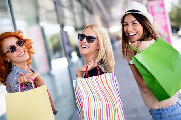 Close-up van jonge gelukkige vrouwen met kleurrijke boodschappentassen