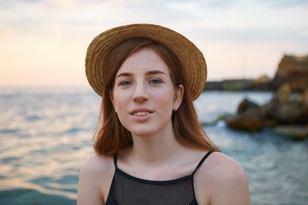 Close up van jonge gember schattige sproeten vrouw draagt hoed, glimlacht en kalmerende kijkt naar de camera. ziet er dromerig en gelukkig uit.