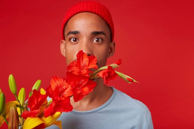 Close up van jonge geschokt man in rode hoed en blauw t-shirt, houdt een boeket in zijn handen en bedekte mond met bloemen, kijkt naar de camera met wijd open ogen, staat over rode achtergrondgeluid.