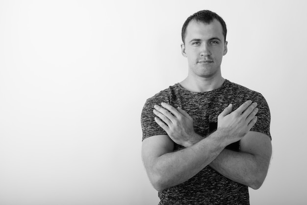 Close-up van jonge gespierde man geïsoleerd met beide armen gekruist op de borst