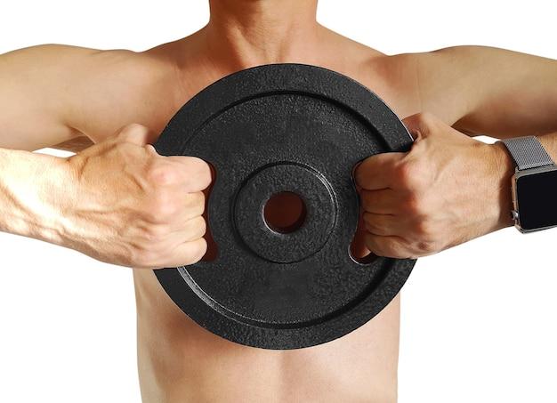 Close-up van jonge gezonde atletenmens die met grote spieren schijfgewichten houden
