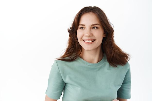 Close-up van jonge hoopvolle vrouwelijke student die opzij kijkt met een tevreden, vastberaden glimlach, het lezen van uw promotionele tekstlogo op kopieerruimte, staande tegen de witte muur