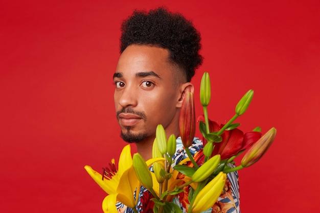 Close-up van jonge kalme donkere man, draagt in hawaiiaans overhemd, houdt gele en rode bloemen boeket, staat op rode achtergrond.