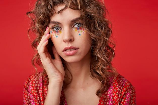 Close-up van jonge krullende vrouw met veelkleurige stippen op haar gezicht haar gezicht zachtjes aanraken met de palm, kijken met kalm gezicht, permanent