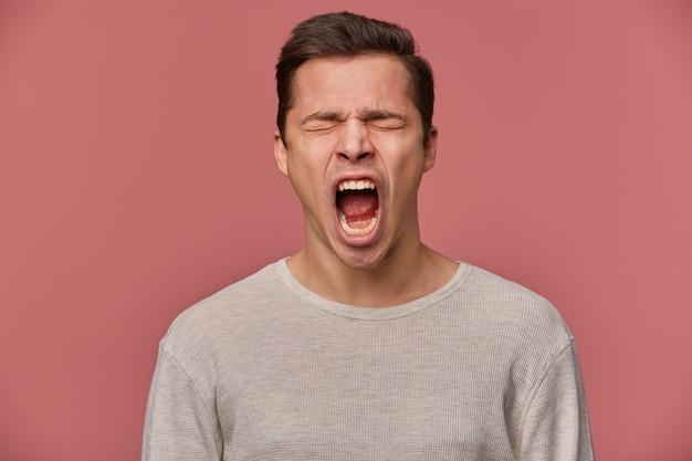 Close up van jonge kwaad aantrekkelijke kerel draagt in lege lange mouw, staat op roze achtergrond met gesloten ogen en schreeuwen, kijkt boos en ongelukkig.