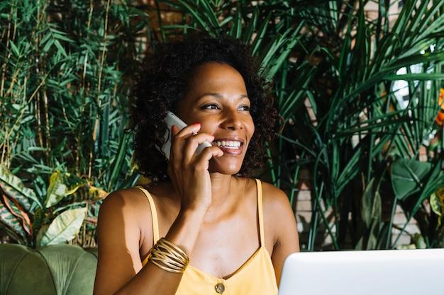 Close-up van jonge lachende vrouw praten op mobiele telefoon