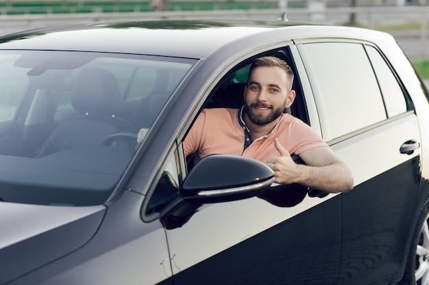 Close up van jonge man die lacht en duimen opdagen in zijn nieuwe auto. een auto kopen.