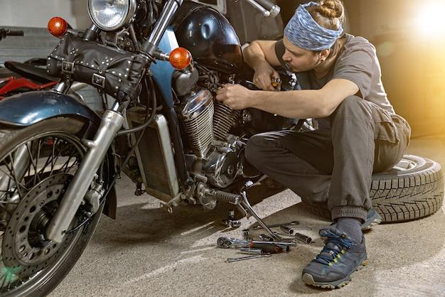 Close-up van jonge man die vintage motorfiets inspecteert in reparatiewerkplaats deze fiets zal perfect zijn