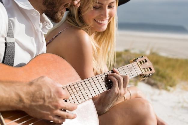 Close up van jonge man een akoestische gitaar spelen op het strand