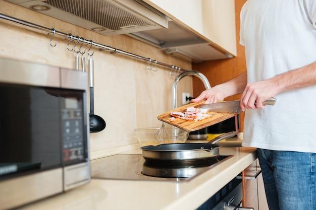 Close-up van jonge man frituren ontmoeten met behulp van pan op de keuken