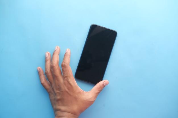 Close up van jonge man hand met een slimme telefoon op blue