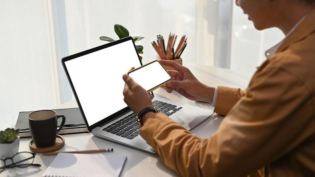Close-up van jonge man met horizontale slimme telefoon en het gebruik van laptopcomputer op kantoor aan huis.