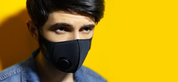 Close-up van jonge man met zwart ademhalingsmasker tegen coronavirus op gele achtergrond met kopie ruimte.