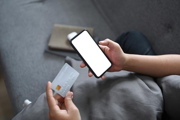 Close-up van jonge man zittend op de bank en online winkelen of online bakken met slimme telefoon.