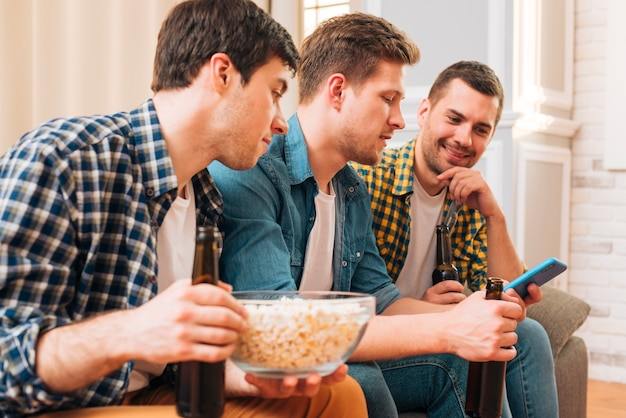 Close-up van jonge mannen die op bank zitten die smartphone bekijken