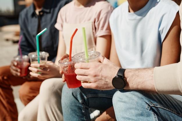Close-up van jonge mensen die cocktails houden terwijl ze genieten van de zomer in het zonlicht, kopieer ruimte