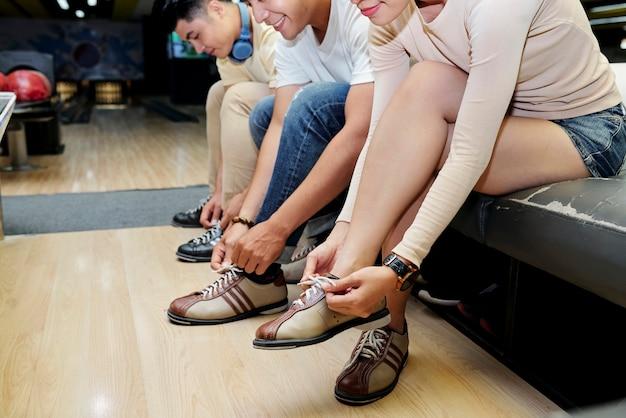 Close-up van jonge mensen die zich voorbereiden op een bowlingspel dat de speciale schoenen aantrekt
