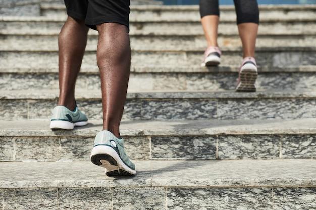 Close-up van jonge mensen in sportschoenen die de trap opgaan terwijl ze buiten trainen