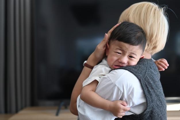 Close up van jonge moeder met huilende baby staande in de woonkamer