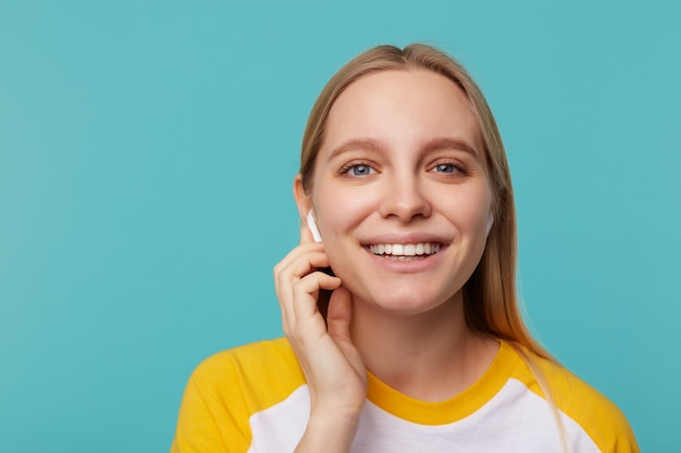 Close-up van jonge mooie blauwogige witharige vrouw die positief kijkt met een charmante glimlach terwijl ze luistert naar muziek in haar oordopjes, geïsoleerd op blauw