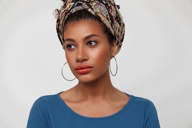 Close-up van jonge mooie donkerharige krullende vrouw met verzameld krullend haar aandachtig opzij kijken terwijl staande op witte achtergrond met handen naar beneden