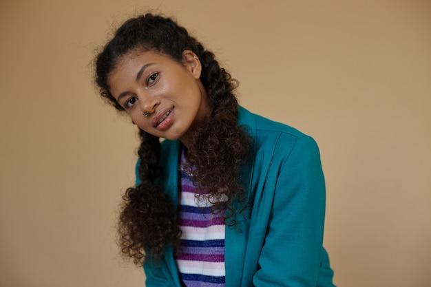 Close-up van jonge mooie krullende brunette vrouw met donkere huid, gekleed in haar gevlochten haar, positief op zoek met een lichte glimlach