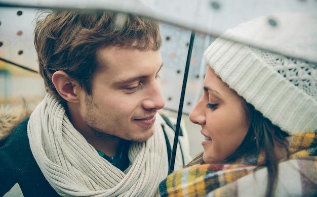 Close-up van jonge mooie paar kijken elkaar met liefde onder de paraplu in een regenachtige herfstdag. liefde en paar relaties concept.