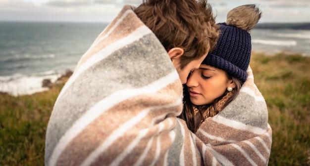 Close-up van jonge mooie paar omarmen onder deken in een koude dag met zee en donkere bewolkte hemel op de achtergrond