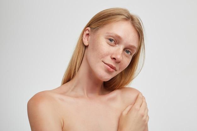 Close-up van jonge mooie roodharige vrouw met natuurlijke make-up die positief kijkt met zachte glimlach en opgeheven palm op haar schouder houdt, geïsoleerd over witte muur
