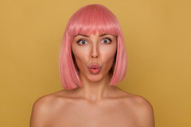 Close-up van jonge mooie roze harige vrouw met kort trendy kapsel rond haar blauwe ogen terwijl ze verbaasd naar de camera kijkt, haar lippen pruilt terwijl ze zich voordeed op mosterd achtergrond