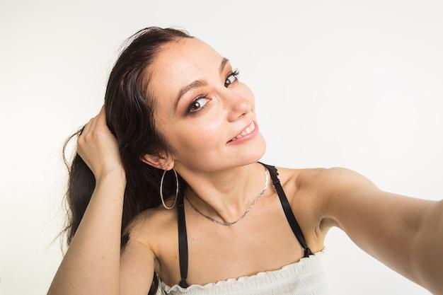 Close-up van jonge mooie vrouw die selfie op witte achtergrond neemt.