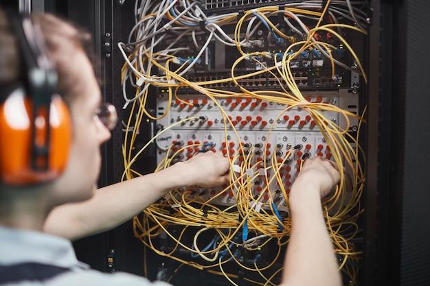 Close up van jonge netwerkingenieur die kabels aansluit in serverruimte tijdens onderhoudswerkzaamheden in datacenter, kopieer ruimte