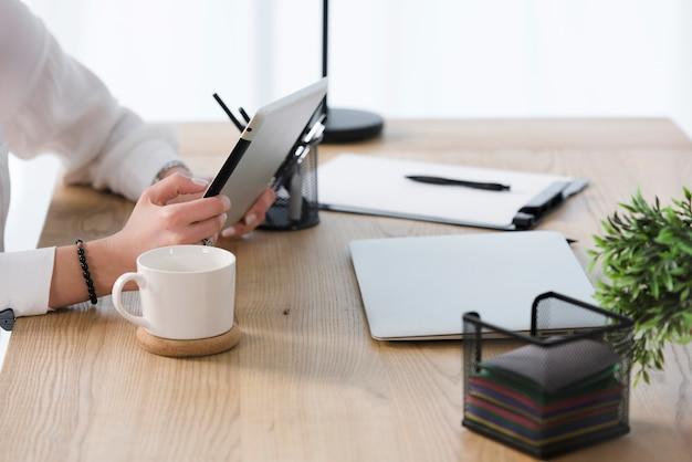 Close-up van jonge onderneemster die digitale tablet met koffiekop gebruikt; laptop op houten tafel