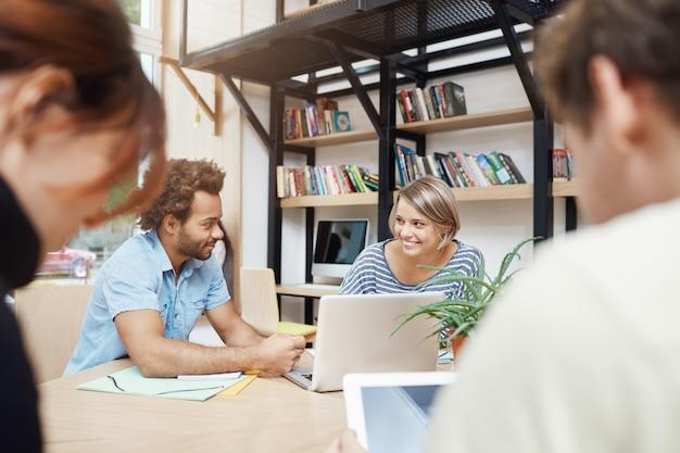 Close up van jonge ontwerpers team zitten in coworking ruimte aan tafel, praten over winsten van oude projecten, statistieken doorzoeken op laptop, gesprek