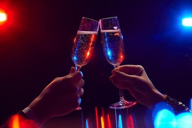 Close up van jonge paar rammelende champagneglazen verlicht door feestverlichting tegen zwarte achtergrond, kopieer ruimte