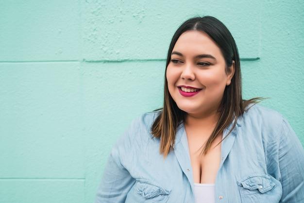 Close-up van jonge plus size vrouw die lacht terwijl staande tegen een lichtblauwe muur buitenshuis.