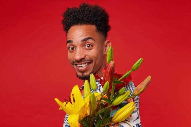 Close-up van jonge positieve donkere man, draagt in hawaiiaans shirt, kijkt naar de camera met gelukkige uitdrukking, houdt gele en rode bloemen, staat op rode achtergrond en glimlacht.