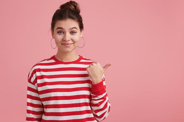 Close-up van jonge schattige vrouw geïsoleerd over roze muur, vestigt terloops uw aandacht op wat er aan de linkerkant is