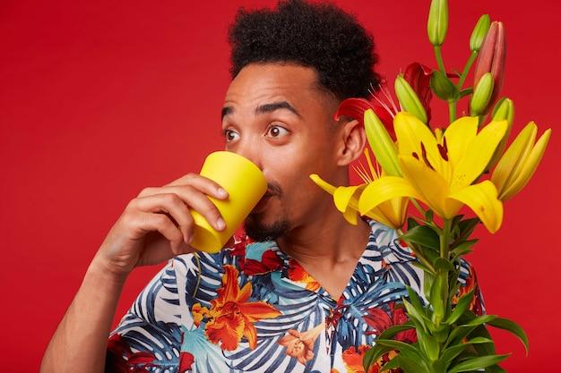 Close-up van jonge verrast afro-amerikaanse man in hawaiiaans shirt, kijkt weg en drinkwater uit een geel glas, houdt gele en rode bloemen boeket, staat op rode achtergrond.