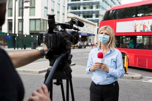 Close-up van jonge verslaggever die een situatie live beschrijft
