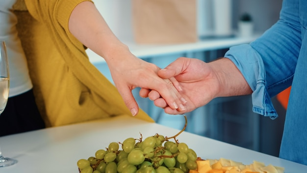 Close-up van jonge vriend die verlovingsring aan zijn vriendin in de moderne luxe keuken zet tijdens familiedag. man die de glanzende ring op zijn vrouwelijke vinger plaatst in de eetkamer.