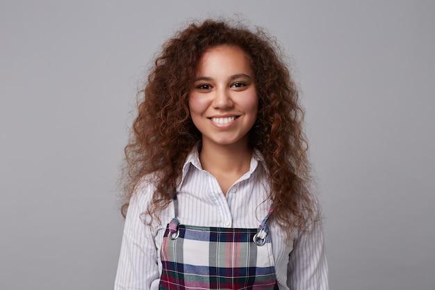 Close-up van jonge vrij gelukkige brunette dame gekleed in wit overhemd kijkt graag met een brede glimlach terwijl wordt geïsoleerd op grijs