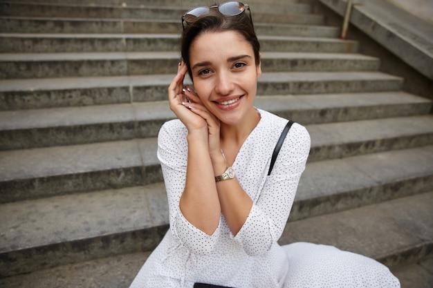 Close-up van jonge vrij positieve donkerharige vrouw die met charmante glimlach kijkt, zonnebril op haar hoofd draagt en opgeheven handpalmen samen vouwt