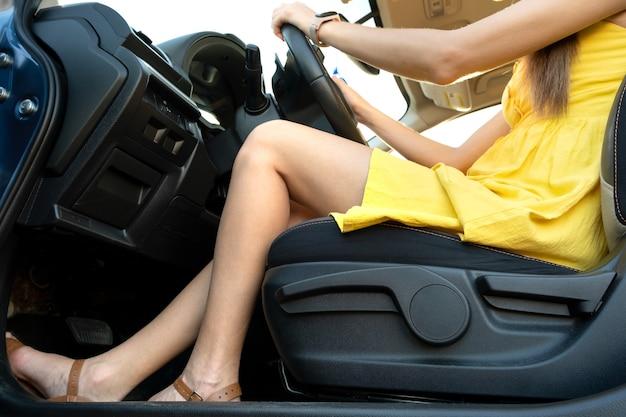 Close up van jonge vrouw bestuurder benen in gele zomerjurk zittend achter het stuur van een auto.