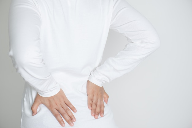 Close-up van jonge vrouw die aan rugpijn lijdt