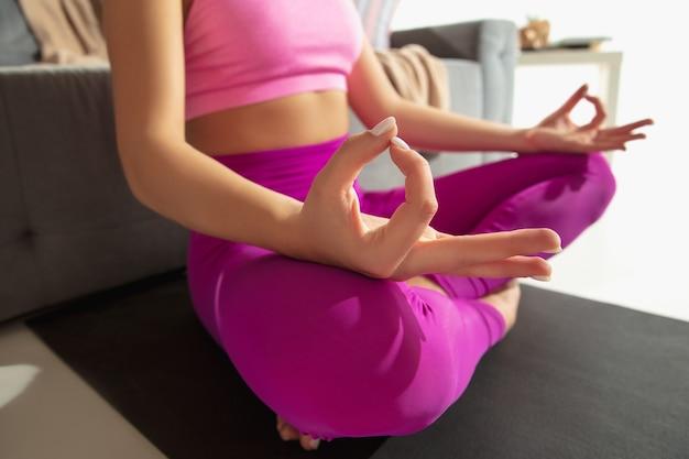 Close-up van jonge vrouw die binnenshuis aan het trainen is, yoga-oefening doet op grijze mat thuis